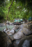 SUV in the tropical jungle - March 7, 2013 Adventure car enthusiast wading a rocky river  using modified four wheel car Stock Photos