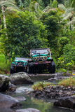 SUV in the tropical jungle - March 7, 2013 Adventure car enthusiast wading a rocky river  using modified four wheel car. SUV in the tropical jungle - March 7 Stock Images