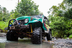 SUV in the tropical jungle - March 7, 2013 Adventure car enthusiast wading a rocky river  using modified four wheel car Royalty Free Stock Images