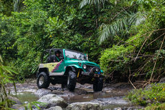 SUV in the tropical jungle - March 7, 2013 Adventure car enthusiast wading a rocky river  using modified four wheel car Stock Photo