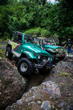 SUV in the tropical jungle - March 7, 2013 Adventure car enthusiast wading a rocky river  using modified four wheel car Royalty Free Stock Photos