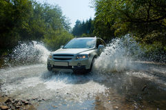 SUV in un flusso della montagna Immagini Stock
