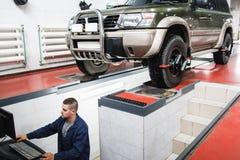 SUV undergoing auto wheel alignment in garage. SUV Car Maintenance Auto Service Diagnostics Garage Repair Shop Mechanics Modern Concept royalty free stock photos