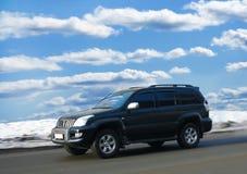 SUV va en el camino del invierno Foto de archivo libre de regalías