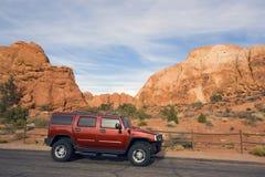 SUV vermelho de encontro às rochas Imagens de Stock