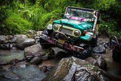 SUV w tropikalnej dżungli - Marzec 7, 2013 przygod samochodowych entuzjast watuje skalistą rzekę używać modyfikującego cztery kół Zdjęcie Stock
