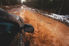 Suv 4wd car rides through muddy puddle, off-road track road, with a big splash, during a jeeping competition Royalty Free Stock Image