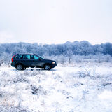 SUV in winter countryside. A view of a clean, modern sports utility vehicle (SUV) in open countryside near woods covered with frost and snow Royalty Free Stock Image