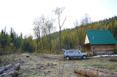 SUV in the wooded mountains, near the hunting lodge. Russia royalty free stock image