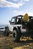 SUV y tabla hawaiana en la playa Imágenes de archivo libres de regalías