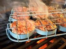 Suwaka stojak z wieprzowina hamburgerami na grillu Zdjęcie Stock