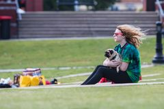 Young Woman Lovingly Holds Pug At Dog Festival. Suwanee, GA, USA - May 6, 2017:  A young woman lovingly holds her pug dog while sitting on the grass at Woofstock Royalty Free Stock Photo