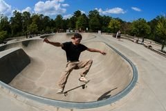 Man Performs Midair Trick In Bowl At Skateboard Park. Suwanee, GA, USA - September 16, 2017: A young man executes a midair skateboard trick in the skateboard royalty free stock photos