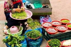 Suwon, Corea del Sud - 25 giugno 2017: Donna del venditore che vende le verdure stagionali sul mercato di strada alla città a Suw immagine stock