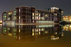 Building in the water at Suytkade in Helmond. At Suytkade in Helmond buildings are situated in the water. At night the calm water works like a mirror, reflecting royalty free stock photos