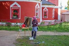 Suzdal, Rusia 16 de agosto de 2015 Un artista de la calle en la ciudad vieja dibuja de la iglesia foto de archivo