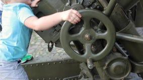 SUZDAL, RUSIA - 8 de mayo de 2019: el niño pequeño da vuelta a la rueda en el arma de la artillería, primer almacen de video