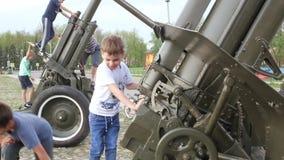 Suzdal, Rusia - 8 de mayo de 2019: los muchachos suben el arma de la artillería, las manijas de la vuelta y la rueda almacen de metraje de vídeo