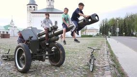 SUZDAL, RUSIA - 8 de mayo de 2019: los niños pequeños suben en el barril de arma de la artillería almacen de video