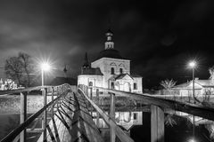 Suzdal, Russia. wooden bridge through the Kamenka River. To Church of Epiphany and Nativity Cathedral of Suzdal Kremlin at night in summer Royalty Free Stock Photos