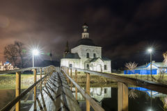 Suzdal, Russia. wooden bridge through the Kamenka River. To Church of Epiphany and Nativity Cathedral of Suzdal Kremlin at night in summer Royalty Free Stock Photography