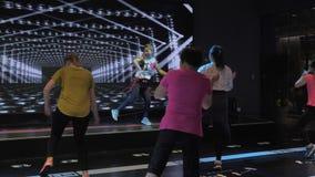 Suzhou Kina - November 6, 2018: Kvinnor av olika åldrar med lagledaren som studerar zumbadansbeståndsdelar, i att dansa grupp stock video