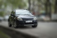 Suzuki black car. Suzuki black car on blurred in motion background royalty free stock photography