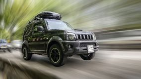 Car of Suzuki. Suzuki car with a roof rack on blurred background in motion stock image