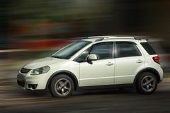 Suzuki white car. Suzuki white car on blurred in motion background royalty free stock photography