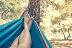 Svänga i en hängmatta och tycka om att campa som är utomhus- arkivfoton