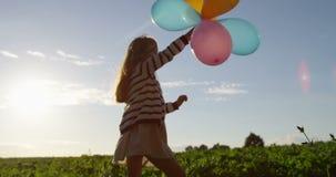 Svänga med lilla flickan för luftballonger som ler i fältet på sommarsolnedgång stock video