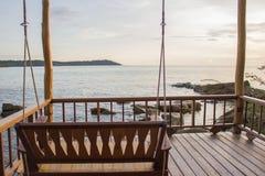Svänga stol på stranden, bakgrund med solnedgång Royaltyfria Bilder