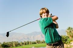 Svängande golfklubb för lycklig Male golfare Royaltyfri Bild