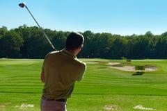 Svängande golfklubb för ung man, bakre sikt Arkivbild