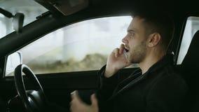 Svära och talande telefon för stressad man, medan sitta inom bilen utomhus arkivfilmer