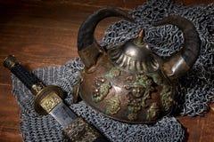 Svärd och soldatens hjälm med horn på en träbakgrund Royaltyfria Bilder