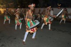 Svärddansare utför längs gatorna av Kandy under Esalaen Perahara i Sri Lanka Royaltyfria Bilder