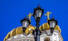 Svärta den sned lyktan med kors på bakgrunden av de guld- kupolerna av den ryska ortodoxa kyrkan Royaltyfri Fotografi