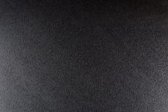 Svärta grov texturerad bakgrund som tänds med dunkelt ljus arkivbild