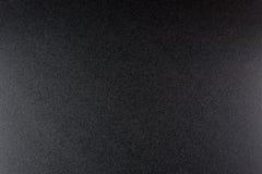 Svärta grov texturerad bakgrund som tänds med dunkelt ljus royaltyfri foto