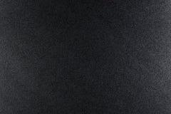 Svärta grov texturerad bakgrund som tänds med dunkelt ljus arkivbilder