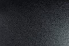 Svärta grov texturerad bakgrund som tänds med dunkelt ljus arkivfoton