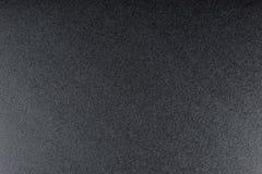 Svärta grov texturerad bakgrund som tänds med dunkelt ljus royaltyfria bilder
