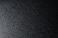 Svärta grov texturerad bakgrund som tänds med dunkelt ljus royaltyfri fotografi