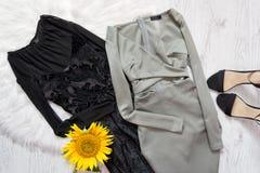 Svärta och gråna klänningen, solrosen och svarta skor på vit päls trendigt begrepp Arkivbild