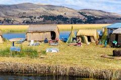 Sväva öar på sjön Titicaca Puno, Peru, Sydamerika som hem halmtäckas Tätt rota att växter Khili väver samman Arkivfoto