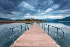 Sväva bron som leder till Agios Achilios, en liten ö på Pre Arkivfoto