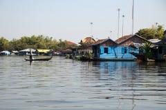 Sväva byn, gamal man i fartyg som navigerar vattenvägen arkivfoton