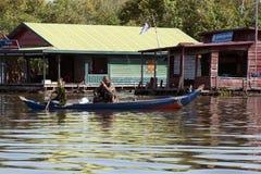 Sväva byn, oidentifierat folk i kanot som passerar polisstationen royaltyfria foton