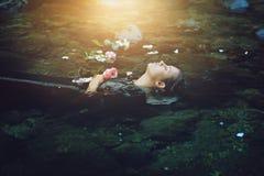 Sväva den döda kvinnan i den mörka floden royaltyfri foto